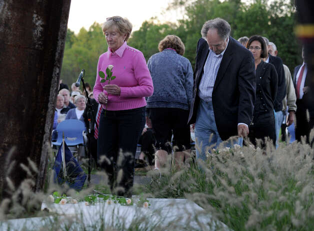 Bobbie Pappas of Ridgefield, lays a flower at the foot of Ridgefield's 9/11 memorial at the close of the towns's Sept. 11 memorial ceremony Tuesday, Set. 11, 2012. Photo: Carol Kaliff / The News-Times