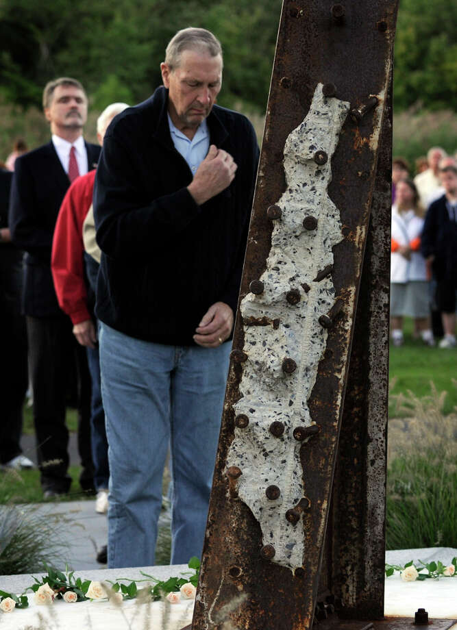 A man makes the sign of the cross after placing a flower at the foot of Ridgefield's 9/11 memorial, Tuesday, Sept. 11, 2012. Photo: Carol Kaliff / The News-Times
