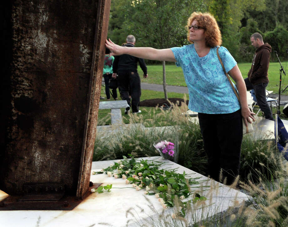 A woman touches the 9/11 memorial after placing a flower at the foot of it at the close of Ridgefield's Sept. 11 memorial ceremony Tuesday, Sept. 11, 2012. Photo: Carol Kaliff