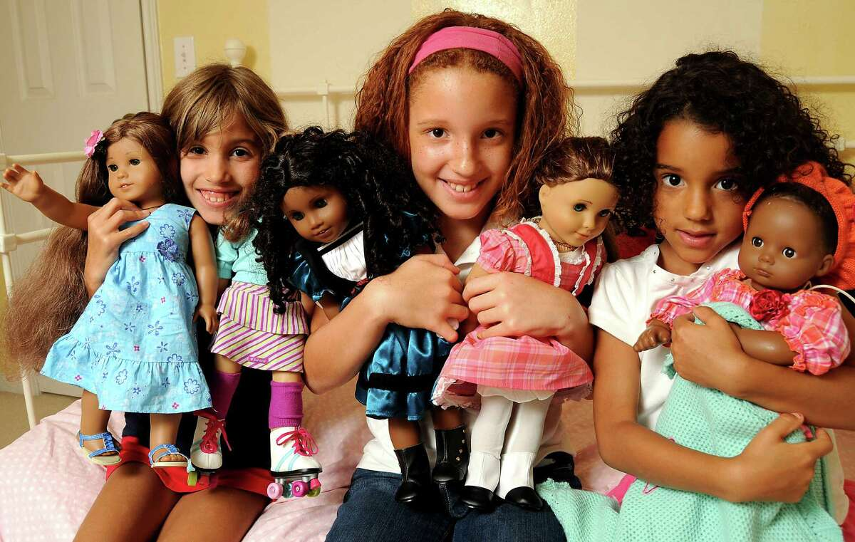 """The Keene sisters, from left, Madeleine, 7, Camille, 9, and Claudia, 5, have five American Girl dolls between them. The Woodlands trio's visit to an American Girl store in St. Louis last year was """"euphoric,"""" says mom."""
