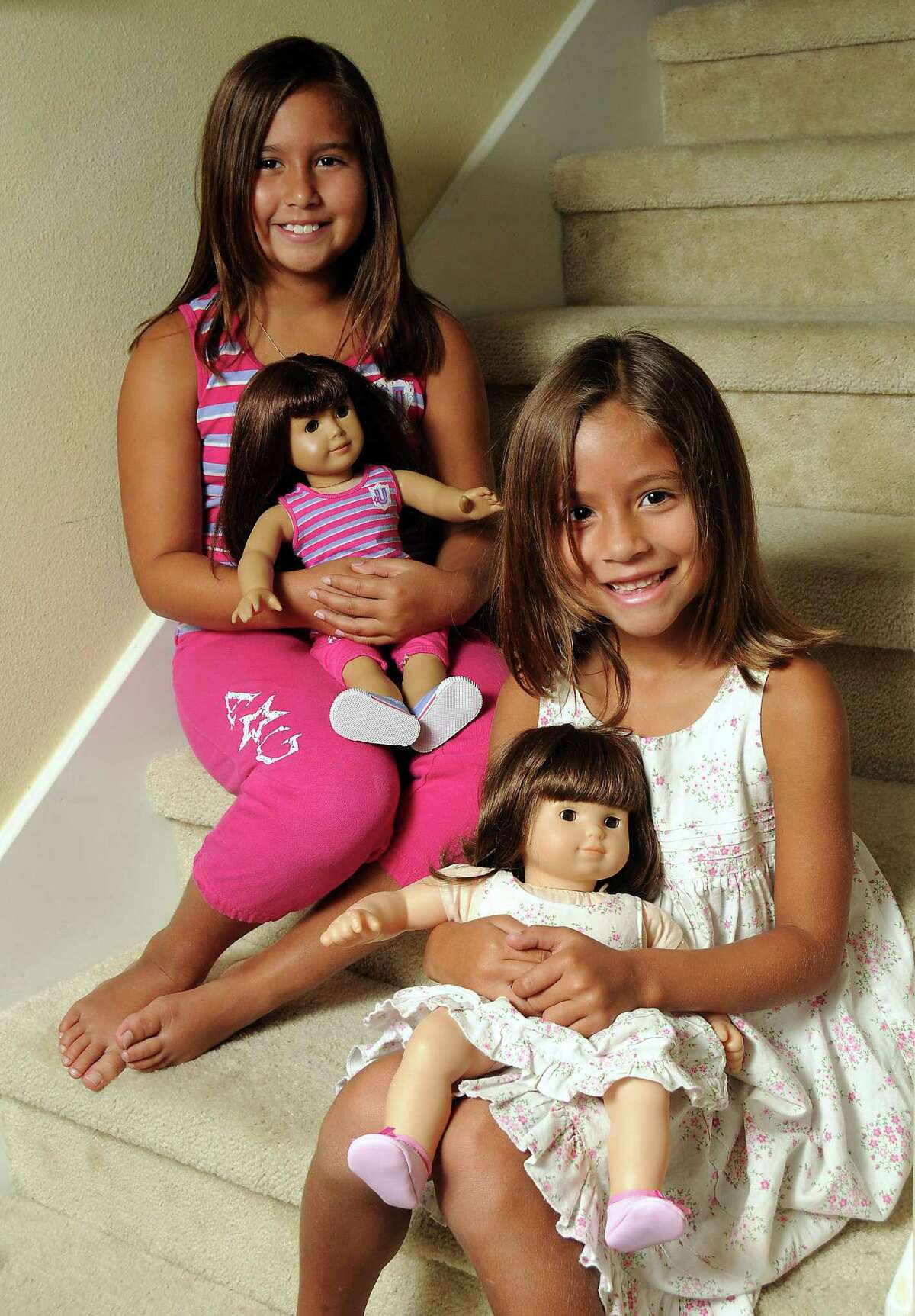 From left: Ashley Rojas, 9, and her sister Gabriela, 5, with their American Girl dolls at home in Richmond Saturday Sept. 8,2012.(Dave Rossman/For the Chronicle)