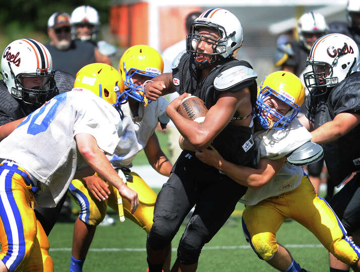 Shelton's Christian Federici is swarmed by Seymour defenders as he runs the football during a scrimm