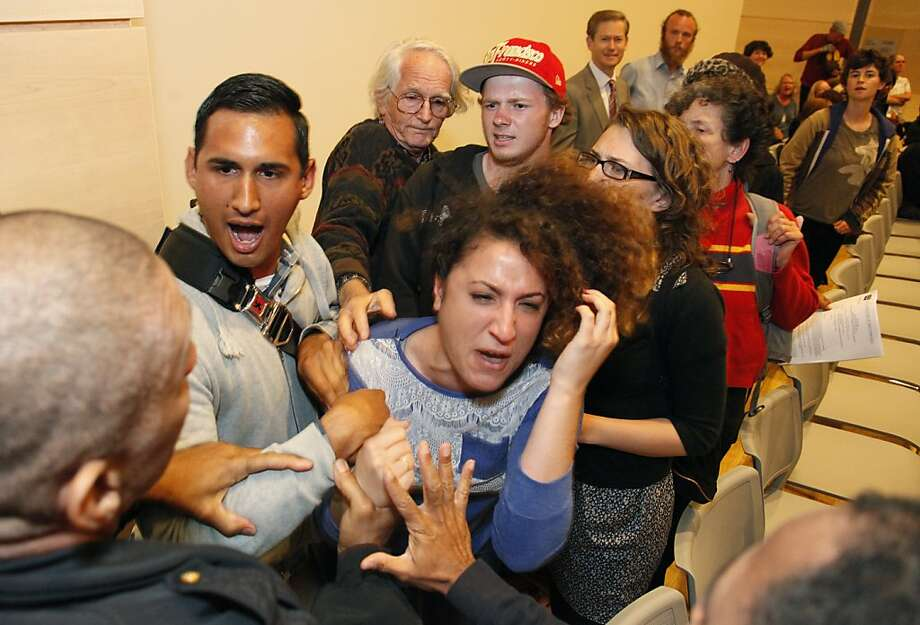 Lalo Gonzalez tries to protect Ali Oligny from being dragged out of the CCSF Board of Trustees meeting by police at City College's Chinatown campus. Photo: Alex Washburn, Special To The Chronicle