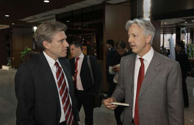 In this Monday, April 11, 2011 file photo, U.S. envoy Chris Stevens, left, speaks with British envoy Christopher Prentice, right, in the lobby of the Tibesty Hotel where an African Union delegation was meeting with opposition leaders in Benghazi.