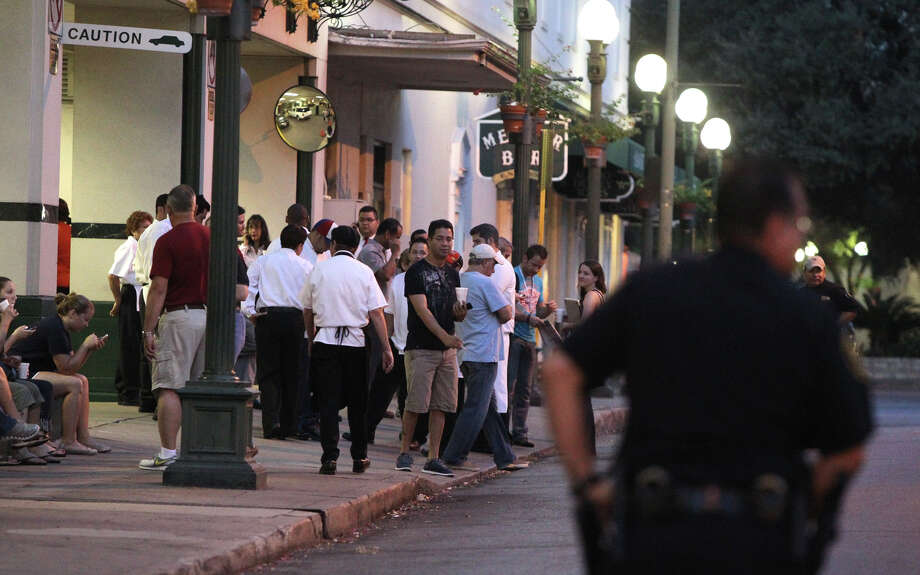 People stand outside of the Menger Hotel early in the morning Wednesday September 12, 2012 after its front desk received a call about a bomb inside of the building. Access to Alamo Plaza was restricted because of the incident and police K-9 dogs were brought in by the police department's bomb squad to clear the building. San Antonio police sergeant Javier Salazar said management relocated some guests during the event but no bomb or package was located after police dogs were brought in. Photo: John Davenport, San Antonio Express-News / San Antonio Express-News