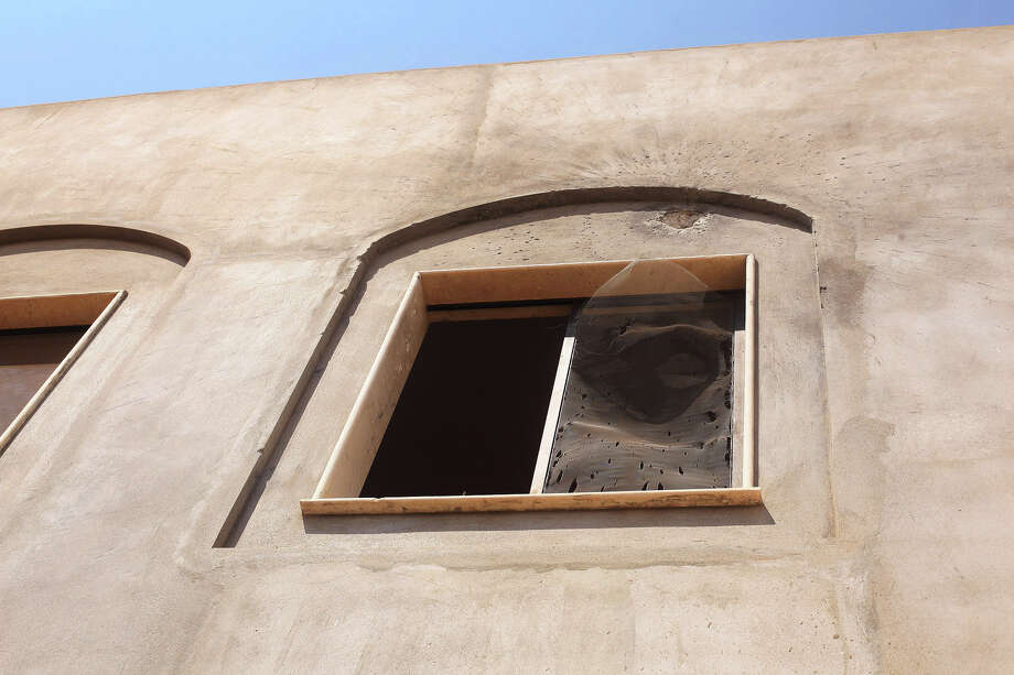A broken window after an attack on the U.S. Consulate by protesters angry over a film that ridiculed Islam's Prophet Muhammad in Benghazi, Libya, Wednesday. The U.S. ambassador to Libya and three other Americans were killed. (AP Photo/Ibrahim Alaguri) Photo: Ap/getty