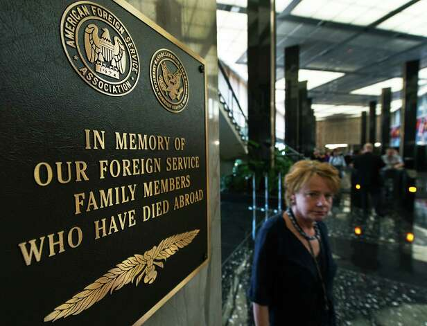 A US State Dept employee walks by one of several plaques honoring its foreign service personell who have died while serving, hanging in the lobby of the US State Department on Wednesday in Washington, DC.  US ambassador to Libya Chris Stevens, at the US consulate compound in Benghazi in the early hours of September 12, 2012, following an overnight attack on the building. Stevens and three of his colleagues were killed in an attack on the US consulate in the eastern Libyan city by Islamists outraged over an amateur American-made Internet video mocking Islam, less than six months after being appointed to his post.    ( PAUL J. RICHARDS/AFP/GettyImages) Photo: PAUL J. RICHARDS, Ap/getty / 2012 AFP