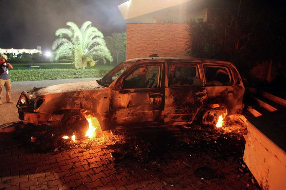 A vehicle sits smoldering in flames after being set on fire inside the US consulate compound in Benghazi late on Wednesday. An armed mob protesting over a film they said offended Islam, attacked the US consulate in Benghazi and set fire to the building, killing one American, witnesses and officials said.          (STR/AFP/GettyImages) Photo: STR, Ap/getty / 2012 AFP