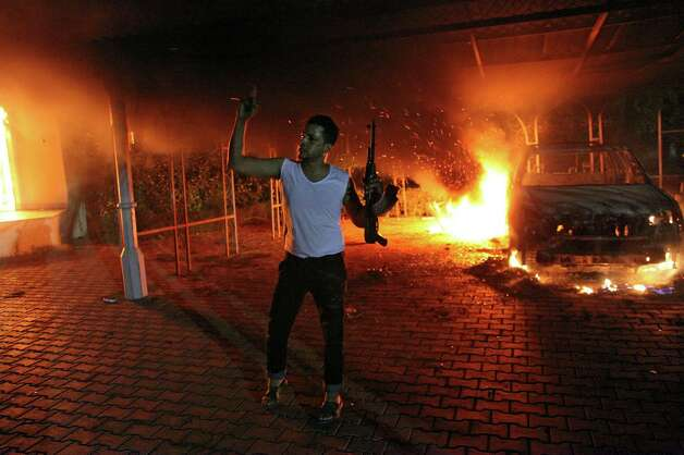 An armed man waves his rifle as buildings and cars are engulfed in flames after being set on fire inside the US consulate compound in Benghazi late on Tuesday. An armed mob protesting over a film they said offended Islam, attacked the US consulate in Benghazi and killed the US ambassador and three other Americans.   (STR/AFP/GettyImages) Photo: STR, Ap/getty / 2012 AFP