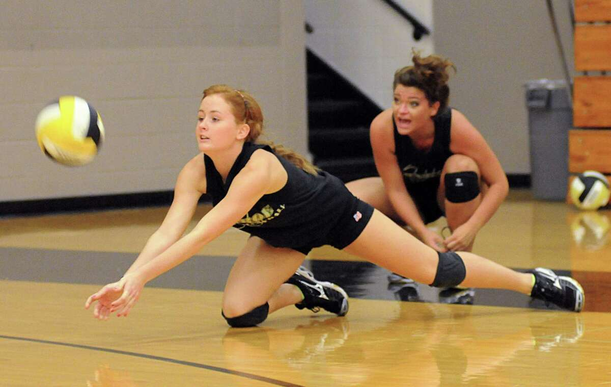 Conroe's Mikie Phillips goes for a dig during a recent practice. Below, the Lady Tigers' Caitlin Hamilton sets the ball during practice at Conroe High School.