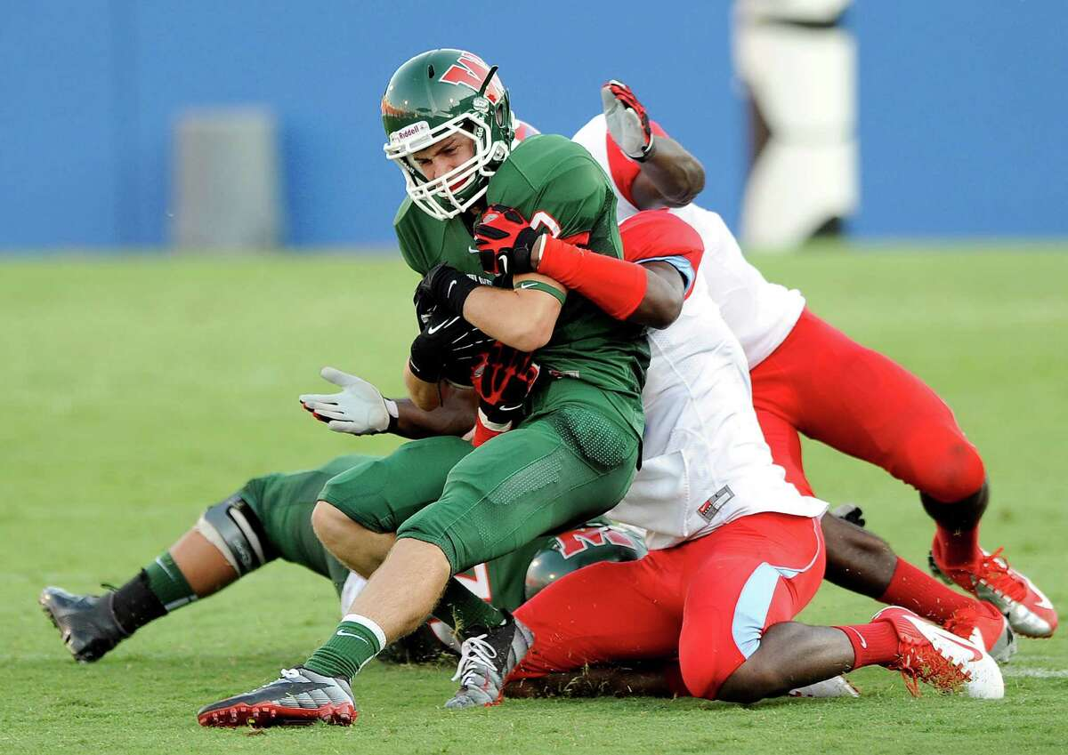The Woodlands' Houston Brown is tackled by a trio of Skyline defenders in the second quarter of the season opener at Cowboys Stadium in Dallas. The Highlanders are 1-1 and face The Woodlands on Saturday.