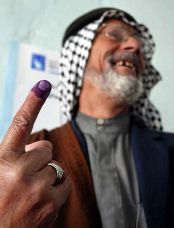 An Iraqi man shows off his ink-stained finger after casting his ballot at a polling station in Jisr Diala on the southern outskirts of Baghdad, Iraq Sunday, Jan. 30, 2005. Voters were required to dip their finger into the ink after voting, in order to prevent people from casting multiple ballots. Photo: JOHN MOORE, AP / AP