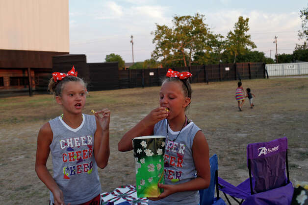 Mathilde Mergaux, 11, left, and Savannah Brown, 10, both of Ft. Worth, eat popcorn as they wait for the movie, Bourne Legacy, to begin at the Brazos Drive-in Theatre in Granbury on Saturday, August 11, 2012. Photo: Lisa Krantz, San Antonio Express-News / San Antonio Express-News