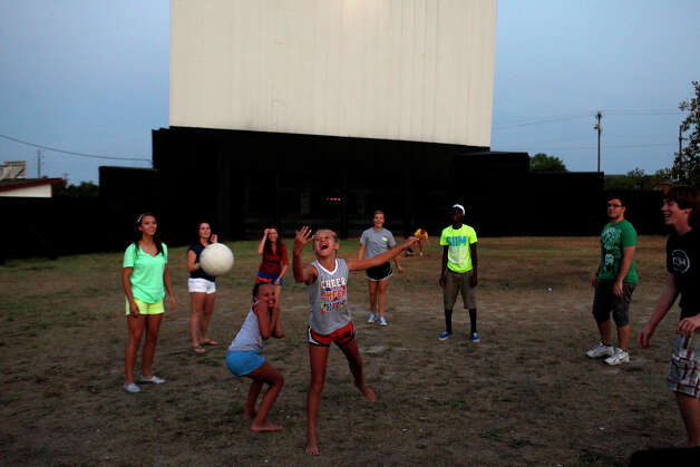 Savannah Brown, 10, left, and Mathilde Mergaux, 11, center, join in a ball game as they wait for the movie to begin at the Brazos Drive-in Theatre in Granbury on Saturday, August 11, 2012. Photo: Lisa Krantz, San Antonio Express-News / San Antonio Express-News