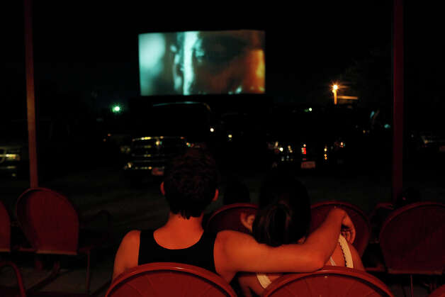 A couple watches Bourne Legacy from the covered seats behind the parking area at the Brazos Drive-in Theatre in Granbury on Saturday, August 11, 2012. Photo: Lisa Krantz, San Antonio Express-News / San Antonio Express-News