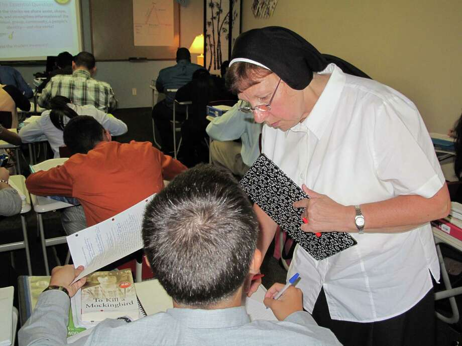 Sister Jude Biank inspects students' progress in her sophomore English class at Cristo Rey High School in East Harlem. 9-10-12. Photo: Tyler Woods