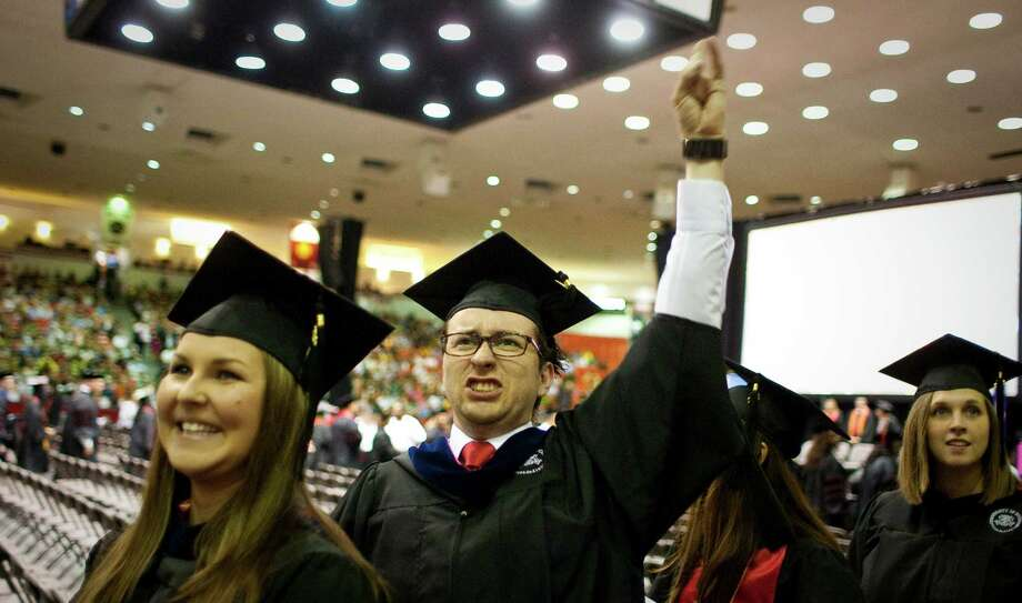 David Stewart, of Houston, waves to friends and family as he walks to his seat with other University of Houston students who are graduating during the Spring 2012 Commencement, Friday, May 11, 2012, in Houston. The colleges of Technology, Education and Hotel and Restaurant Management graduated at the 2 p.m. slot. The College of Business, Law and Optometry graduate tomorrow. Photo: Nick De La Torre, Houston Chronicle / © 2012  Houston Chronicle