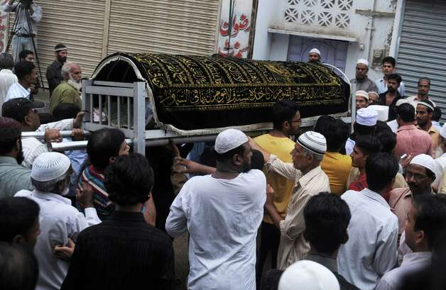 Pakistani Muslims carry the coffin of a garment factory worker during the funeral following a fire in the garment factory in which at least 280 people died in Karachi on September 12, 2012.  Photo: RIZWAN TABASSUM, AFP/Getty Images / AFP