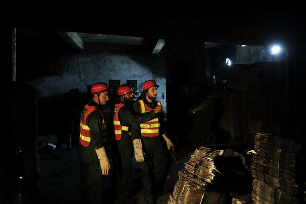 Rescuers collect evidence in a shoe-making factory following a fire which gutted the factory the previous night. Photo: ARIF ALI, AFP/Getty Images / AFP