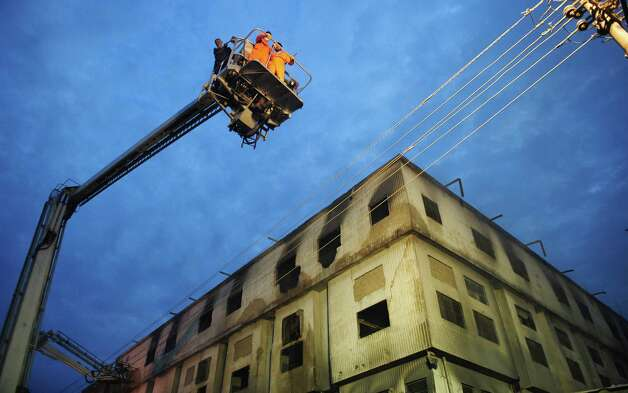 Pakistani firefighters take part of rescue operation in the garment factory in Karachi on September 12, 2012. At least 63 people were killed when a blaze engulfed a garment factory in Pakistan's largest city Karachi, an official said.  Photo: ASIF HASSAN, AFP/Getty Images / AFP