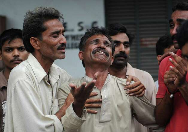 A Pakistani man mourns the death of relatives after a fire erupted in a garment factory in Karachi on September 12, 2012. Photo: ASIF HASSAN, AFP/Getty Images / AFP