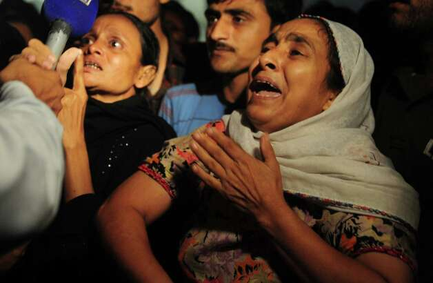 A Pakistani woman mourns the death of her relatives in front of the garment factory in Karachi on September 12, 2012. At least 63 people were killed when a blaze engulfed a garment factory in Pakistan's largest city Karachi, an official said.  Photo: ASIF HASSAN, AFP/Getty Images / AFP