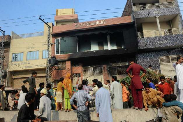 Pakistani people gather outside a shoe-making factory following a fire which gutted the factory the previous night in Lahore on September 12, 2012. More than 240 people have perished in devastating fires that gutted factories in Pakistan's two largest cities, raising fresh concerns about workplace safety, officials said.  Photo: ARIF ALI, AFP/Getty Images / AFP