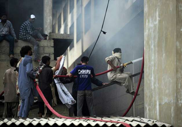 Pakistani firefighters extinguish a fire that erupted in a garment factory in Karachi on September 12, 2012.  More than 240 people have perished in devastating fires that gutted factories in Pakistan's two largest cities, raising fresh concerns about workplace safety, officials said.  Photo: ASIF HASSAN, AFP/Getty Images / AFP