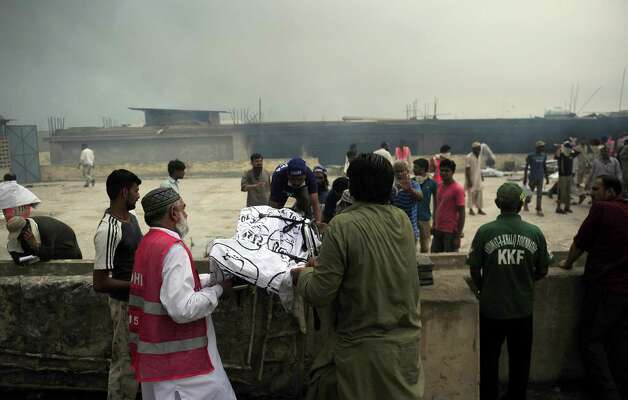 Pakistani rescuers move the dead body of a garment factory worker after fire erupted in the factory in Karachi on September 12, 2012.  More than 240 people have perished in devastating fires that gutted factories in Pakistan's two largest cities, raising fresh concerns about workplace safety, officials said. Photo: ASIF HASSAN, AFP/Getty Images / AFP