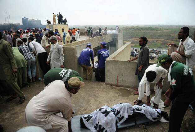 Pakistani rescue workers move a dead body of a garment worker after fire erupted in a garment factory in Karachi on September 12, 2012. More than 240 people have perished in devastating fires that gutted factories in Pakistan's two largest cities, raising fresh concerns about workplace safety, officials said. Photo: ASIF HASSAN, AFP/Getty Images / AFP