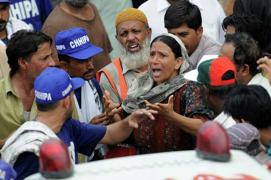 A relative of a Pakistani garment factory worker argues with rescuers outside the factory in Karachi