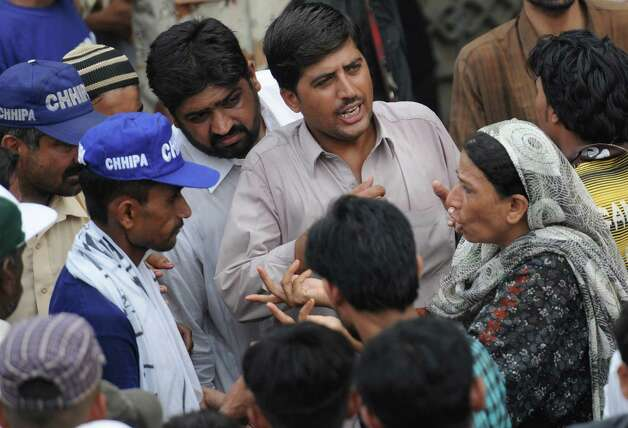 A relative of a Pakistani garment factory worker argues with rescuers outside the factory in Karachi on September 12, 2012. More than 310 people have perished in fires that gutted factories in Pakistan's two largest cities, in tragedies that prompted calls for an overhaul of poor industrial safety standards, officials said.  Photo: ASIF HASSAN, AFP/Getty Images / AFP