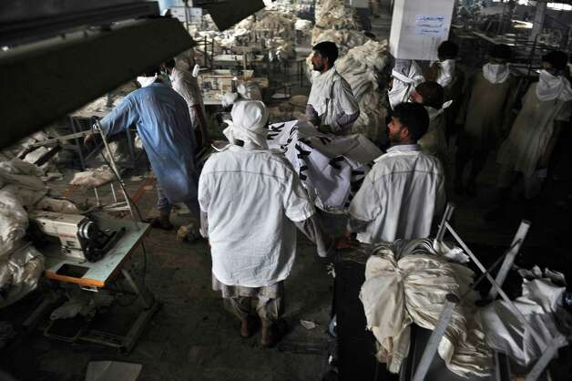 Pakistani rescue workers remove a dead body of a worker from a garment factory following a fire in which at least 280 people died in Karachi on September 12, 2012.  More than 310 people have perished in fires that gutted factories in Pakistan's two largest cities, in tragedies that prompted calls for an overhaul of poor industrial safety standards, officials said .  AFP PHOTO/Rizwan TABASSUMRIZWAN TABASSUM/AFP/GettyImages Photo: RIZWAN TABASSUM, AFP/Getty Images / AFP