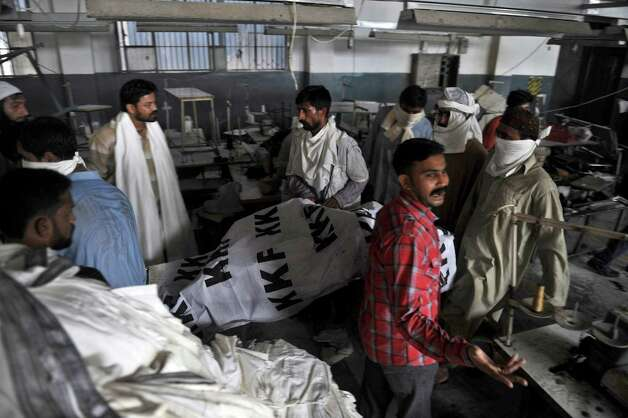 Pakistani rescue workers remove the dead body of a worker from a garment factory following a fire in which at least 280 people died in Karachi on September 12, 2012.  Photo: RIZWAN TABASSUM, AFP/Getty Images / AFP