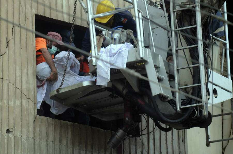 Pakistani rescuers remove a dead body from a garment factory following a fire in which at least 280