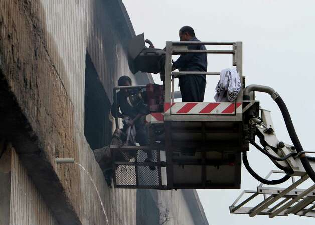 Pakistani rescue workers pull out a dead body from a burnt garment factory in Karachi, Pakistan on Wednesday, Sept. 12, 2012.  Photo: Fareed Khan, Associated Press / AP