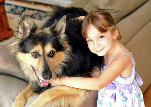 Emilee Ferguson, 4, hugs Nikkita, her dog, in their Sandy Hook home Monday, Aug. 20, 2012. Photo: Michael Duffy / The News-Times
