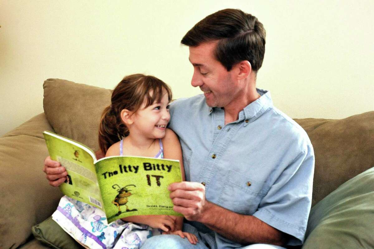 """Emilee Ferguson, 4, and her dad, Scott read from their book """"The Itty Bitty It,"""" in their Sandy Hook home Monday, Aug. 20, 2012."""