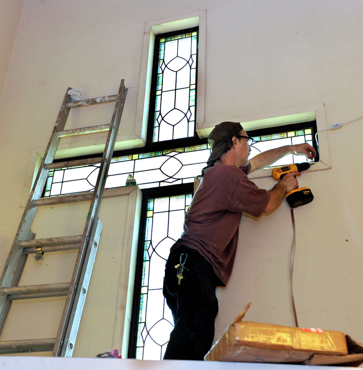 Mark Tomascak, 52, of New Milford, owner of Dragonfly Studios, works on installing a stained glass cross at the New Milford United Methodist Church Wednesday, Sept. 12, 2012.