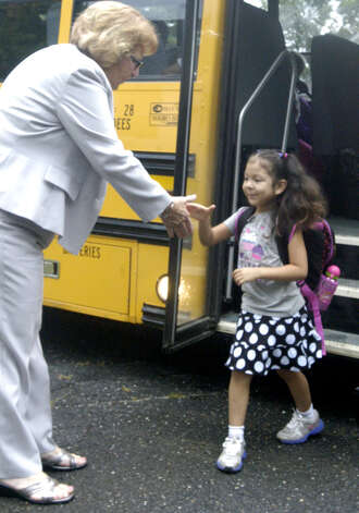Pat Cosentino, the superintendent of schools in Region 12, greets a young Booth Free School student as she gets off the bus on the first day of school, Aug. 28, 2012 Photo: Norm Cummings