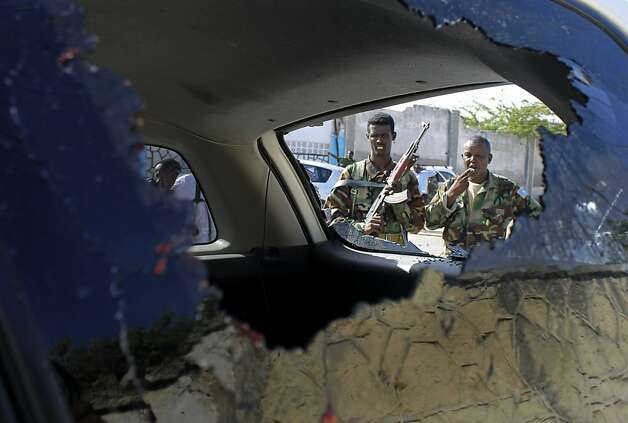 Soldiers are seen through the shattered window of a vehicle outside the hotel home of Somalia's new president. At least five people died in the bombings. Photo: Farah Abdi Warsameh, Associated Press