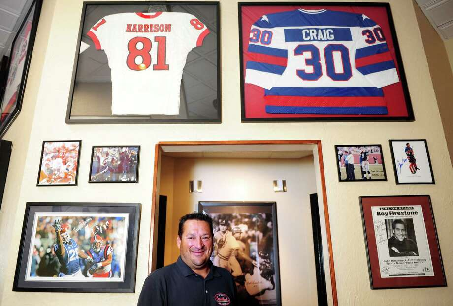 Mark Hirschbeck, a former umpire in Major League Baseball, is surrounded by sports memorabilia at his restaurant, Hirschbeck's Sports Bar and Grill at 882 Bridgeport Avenue in Shelton, including the photo behind him of Hirschbeck breaking up a fight during a game. Photo: Autumn Driscoll / Connecticut Post