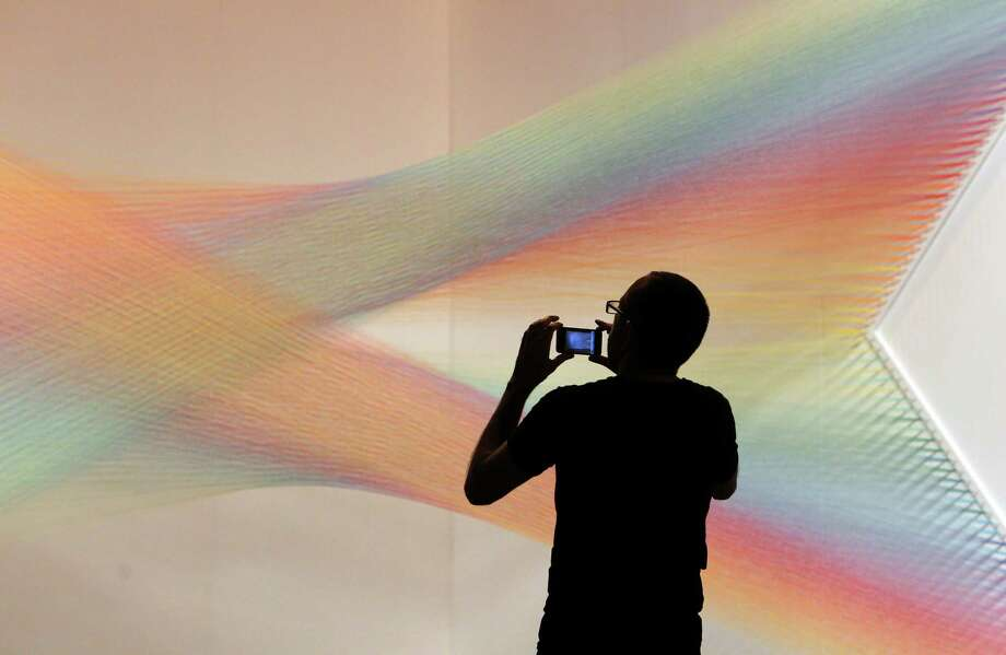 "Artist Gabriel Dawe inspects his installation called ""Plexus C5"" in preparation for the Houston Fine Art Fair at Reliant Center on Wednesday, Sept. 12, 2012, in Houston. The installation has 13 miles of thread zigzagging across boards. Photo: Mayra Beltran, Houston Chronicle / © 2012 Houston Chronicle"
