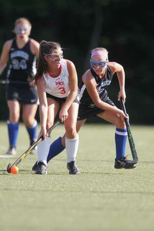 New Canaan field hockey player Bea Eppler looks for an open teammate while Darien Kat Huber defends in the game in New Canaan, Conn. on Wednesday, Sept. 12, 2012. Photo: J. Gregory Raymond / Stamford Advocate Freelance;  © J. Gregory Raymond/for The Advocate