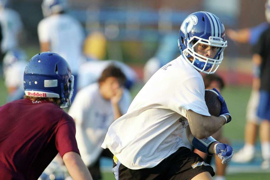 Junior wide receiver John Reid puts a move on DB Brian Wiegand during preseason practice at Darien High School Thursday morning. The Blue Wave, who open against Fairfield Ludlowe in 3 weeks, will rely upon a multi-faceted offense and a swarming defense, as it attends to secure an FCIAC crown. Photo: J. Gregory Raymond / Stamford Advocate Freelance