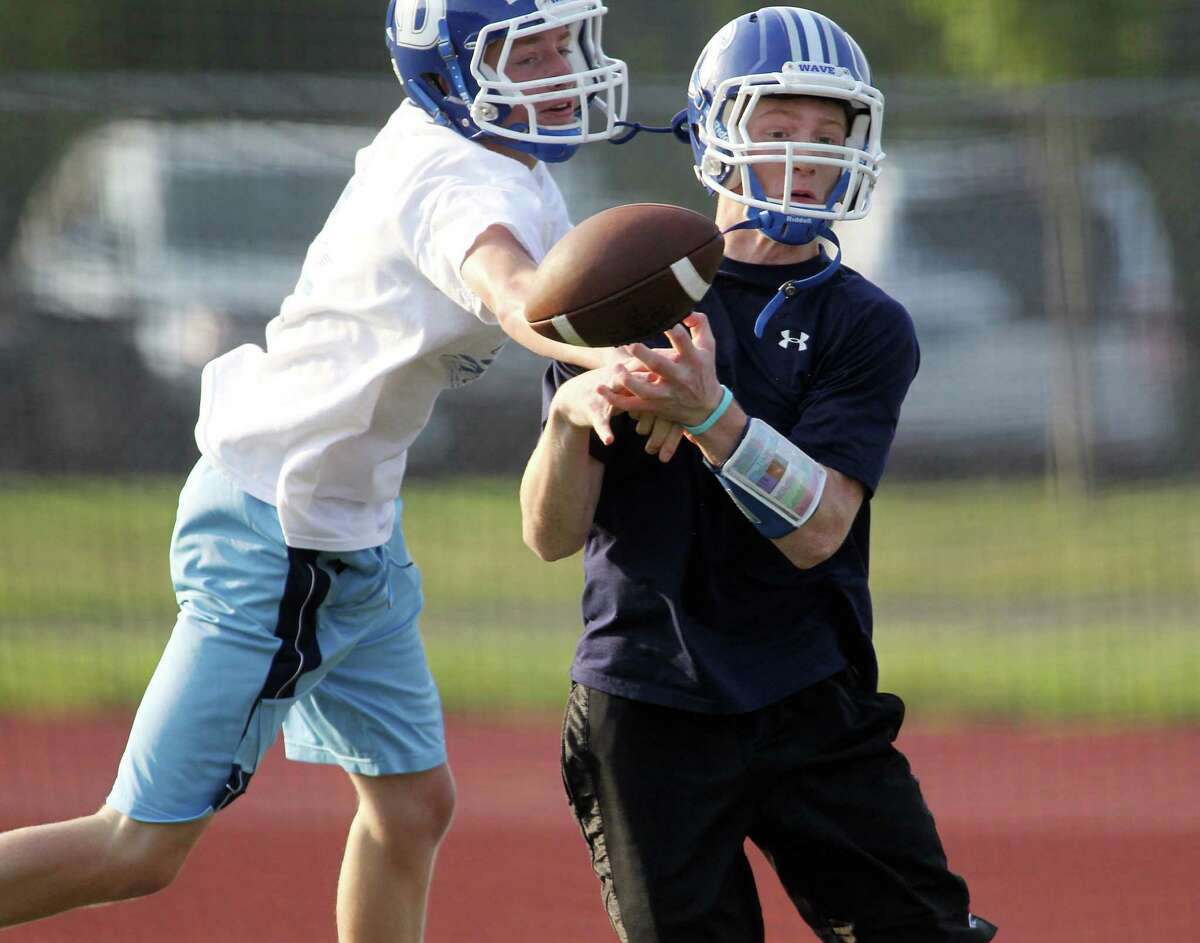 Patrick Reilly battles teammate Nick Lombardo for a pass during preseason conditioning practice at Darien High School. The Blue Wave will again be a force to be reckoned with in FCIAC play this season, as it attempts to go further than last season's 8-2 record.