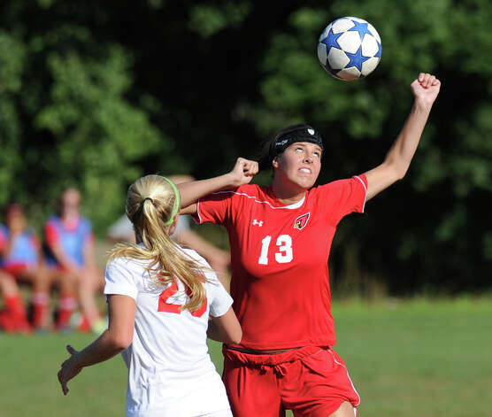 At right, Stephanie Gittings # 13 of Greenwich, heads the ball while being defended by Kelly Armstrong # 25 of New Canaan during the girls high school soccer match between Greenwich High School and New Canaan HIgh School at New Canaan, Wednesday, Sept. 12, 2012. Photo: Bob Luckey / Greenwich Time