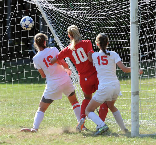 At center, Emily Johnson # 10 of Greenwich scores while being defended by New Canaan players, Anna Borea, # 19, left, and Gabriella Borea # 15, during the girls high school soccer match between Greenwich High School and New Canaan HIgh School at New Canaan, Wednesday, Sept. 12, 2012. Photo: Bob Luckey / Greenwich Time