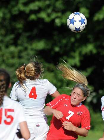 At left, Marina Braccio, # 4 of New Canaan, goes for the ball against Molli Haimerl # 7 of Greenwich, during the girls high school soccer match between Greenwich High School and New Canaan HIgh School at New Canaan, Wednesday, Sept. 12, 2012. Photo: Bob Luckey / Greenwich Time