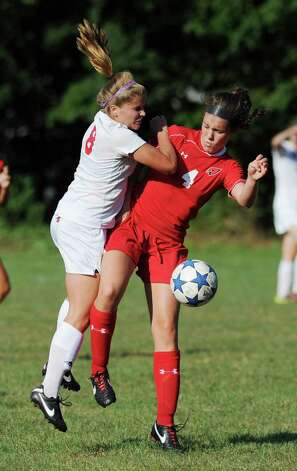 Madeline Carroll, left, # 8 of New Canaan, goes up against Caroline Markowitz, # 4 of Greenwich during the girls high school soccer match between Greenwich High School and New Canaan HIgh School at New Canaan, Wednesday, Sept. 12, 2012. Photo: Bob Luckey / Greenwich Time